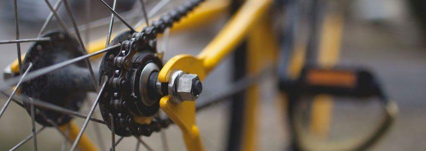 Detailansicht eines gelben Single-Speed-Fahrrads im Bereich der hinteren Radnabe
