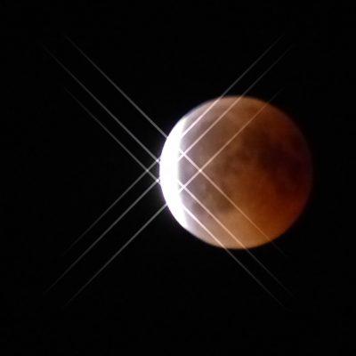 Am linken Rand des roten Vollmondes erscheint mit beginnendem Ende der Mondfinsternis die schmale helle Sichel des zurückkehrenden Lichts.