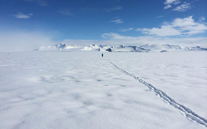 Fußspuren im Schnee der Ankarktis, ein Mensch läuft auf ferne Berge zu