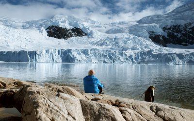 Glaziologe Claude Lorius sitzt neben einem Pinguin und schaut über eine Bucht auf einen Gletscher