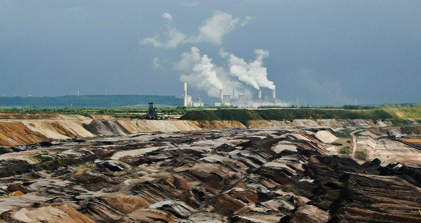 Zerstörte Landschaft durch Braunkohletagebau und Luftverschmutzung durch Kohlekraftwerk